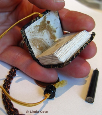 Close up of the handmade mini artist book by Dea Fischer. The inside is a beautiful marbled paper.