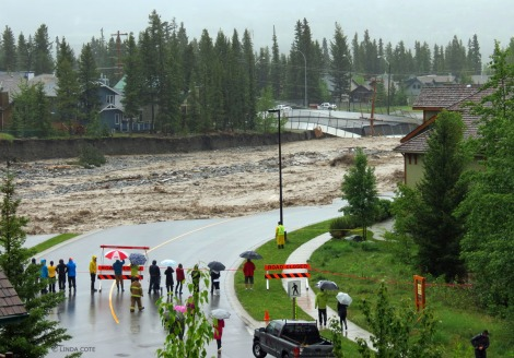 By noon Thursday, June 20, bystanders watch as Canmore's Cougar Creek bursts its banks.